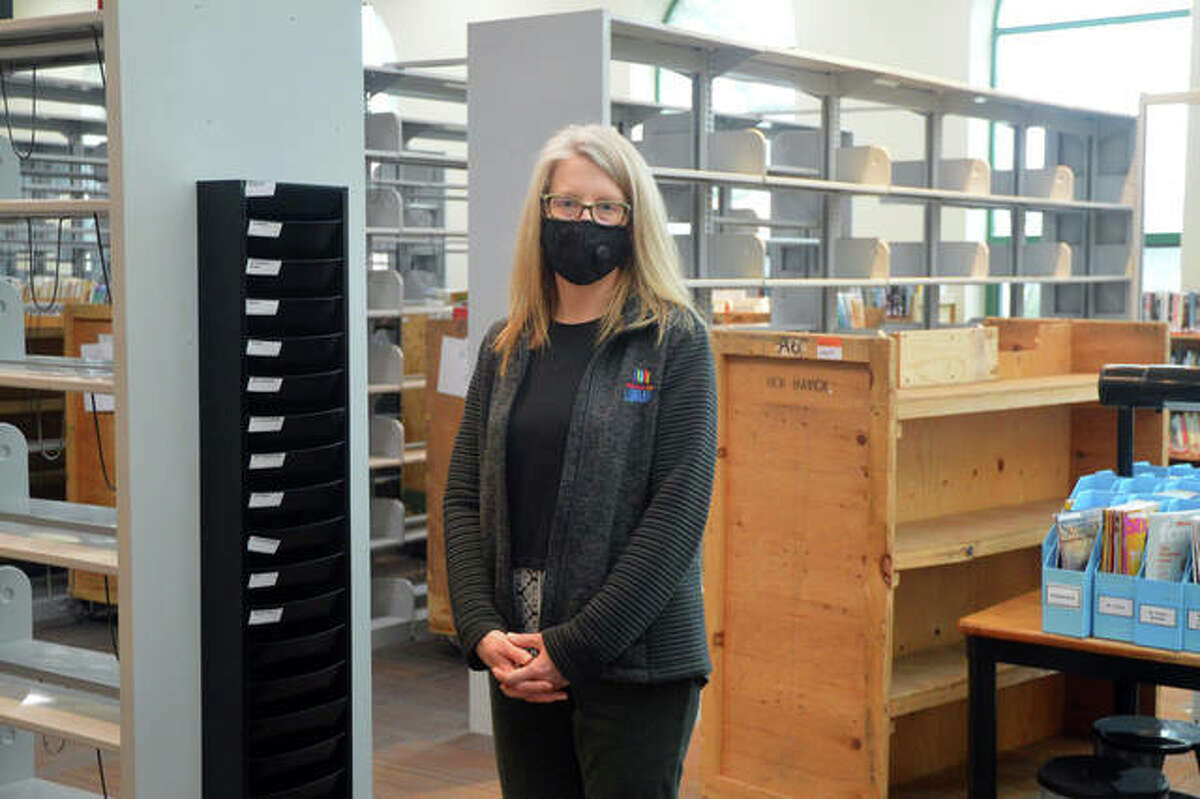 """Jill Schardt, director of the Edwardsville Public Library, stands in front of some of the bookshelves that are being moved as part of """"EPL - The Next Chapter,"""" which will involve the renovation and modernization of the interior of the historic building."""