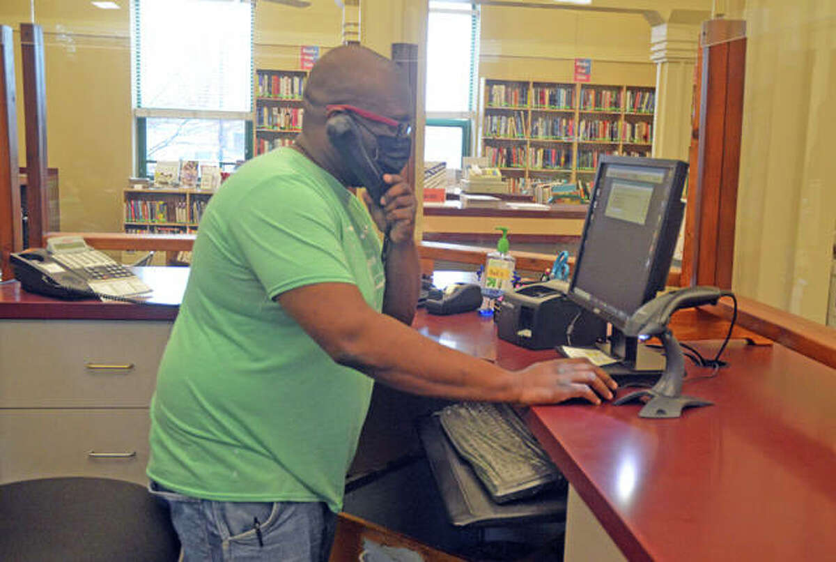 Evan Evans, an employee with the Edwardsville Public Library, answers a patron's phone call on Wednesday.