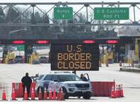 US Customs officers stand beside a sign saying that the US border is closed at the US/Canada border in Lansdowne, Ontario, on March 22, 2020. - The United States agreed with Mexico and Canada to restrict non-essential travel because of the coronavirus, COVID-19, outbreak and is planning to repatriate undocumented immigrants arriving from those countries. (Photo by Lars Hagberg / AFP)