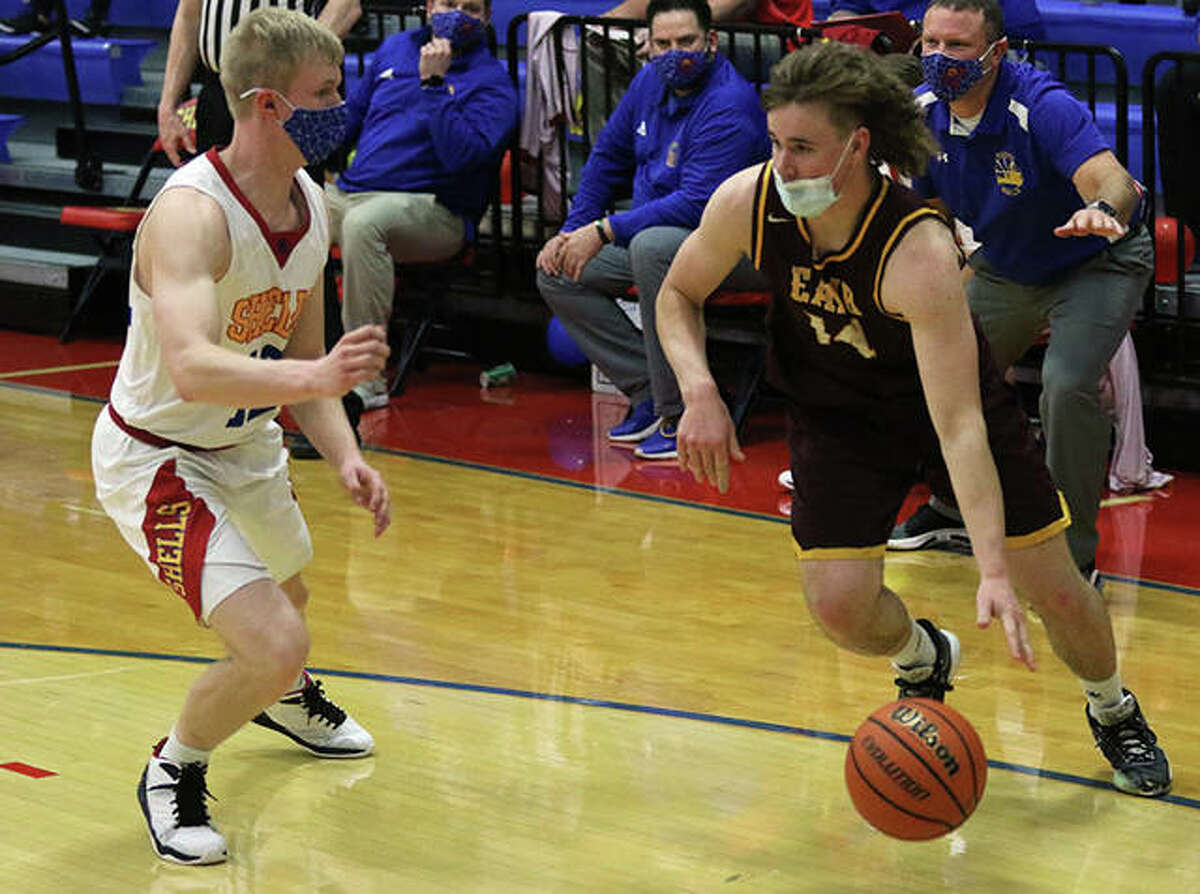 EA-WR's Spencer Slayden (right) drives baseline on Roxana's Cade Slayden in a career-ending boys basketball game for both on March 12 at Larry Milazzo Gym in Roxana. Cade earned bragging rights between the cousins with the Shells defeating the Oilers 56-36.