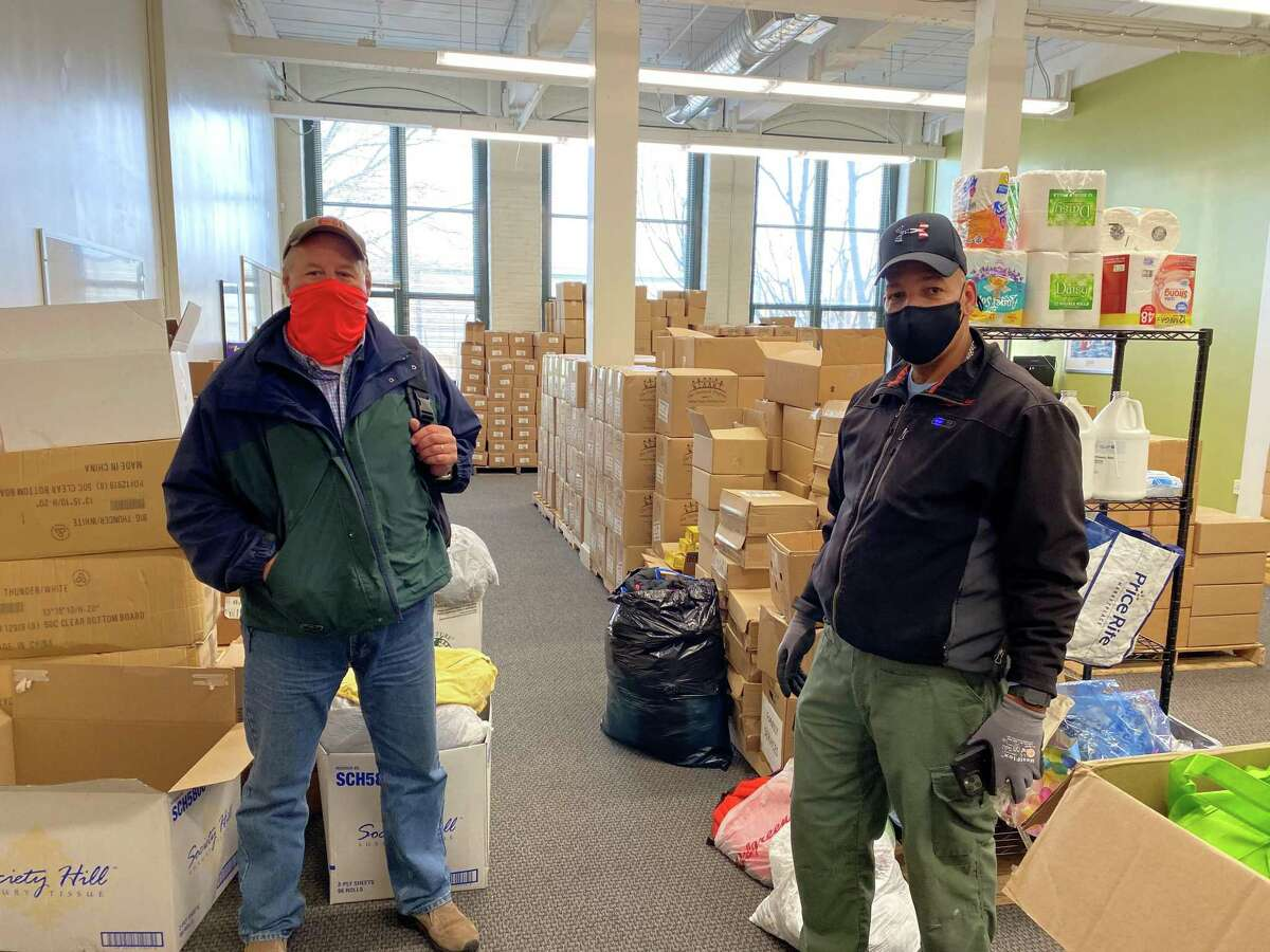 David Sarlitto, Executive Director of the Ocean State Job Lot Charitable Foundation, and Family Service of Rhode Island staff member Dave Cooley, pose in front of a portion of OSJL's PPE/food donation to FSRI.