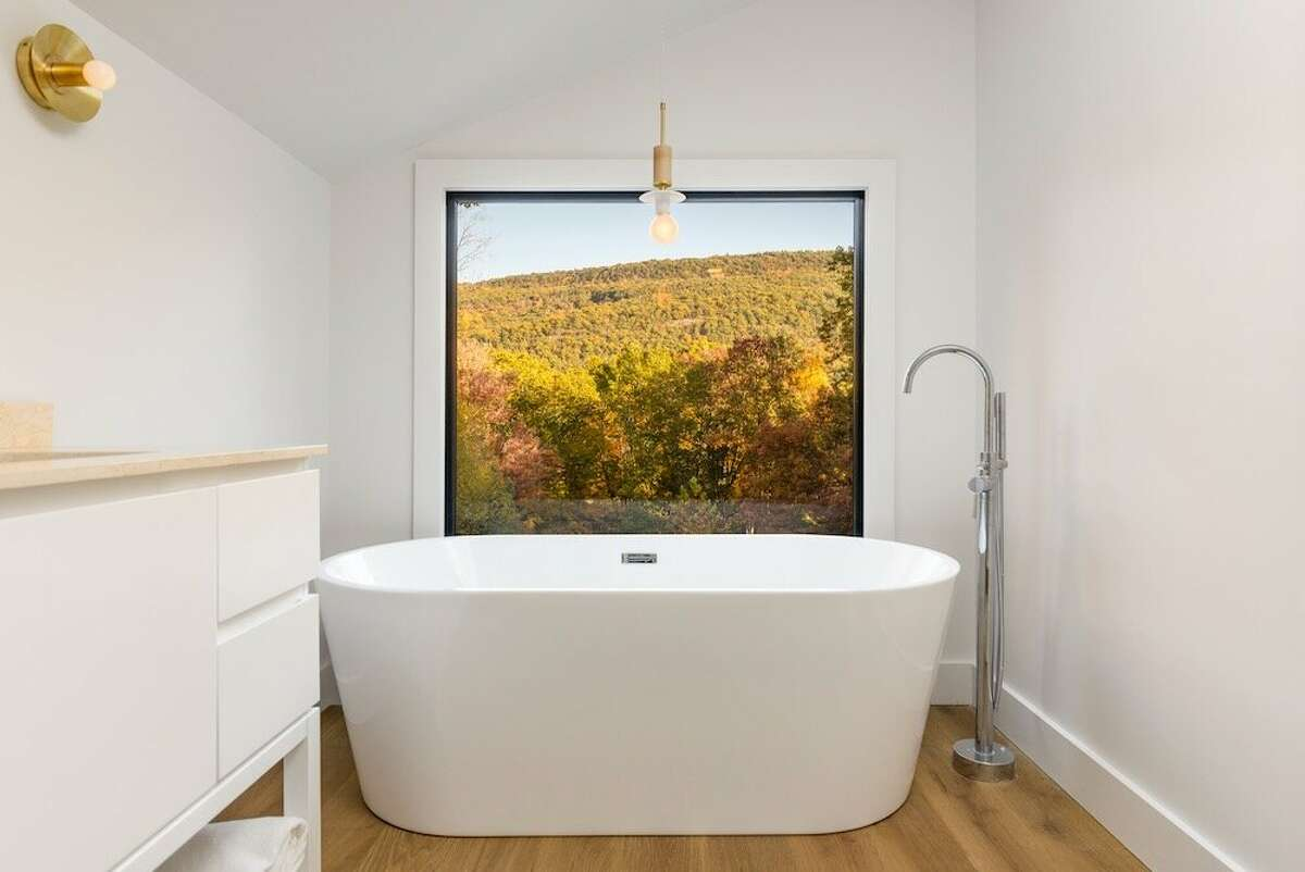 """When Wallach was designing the High Falls house as an Airbnb rental, she envisioned the view from the bathroom being her main selling point. She installed a picture window and a soaking tub from which to enjoy the Mohonk Preserve views. """"I was like, 'This is the money shot of the tub and the mountains...who wouldn't want to sit in this tub and look at this view?'"""""""