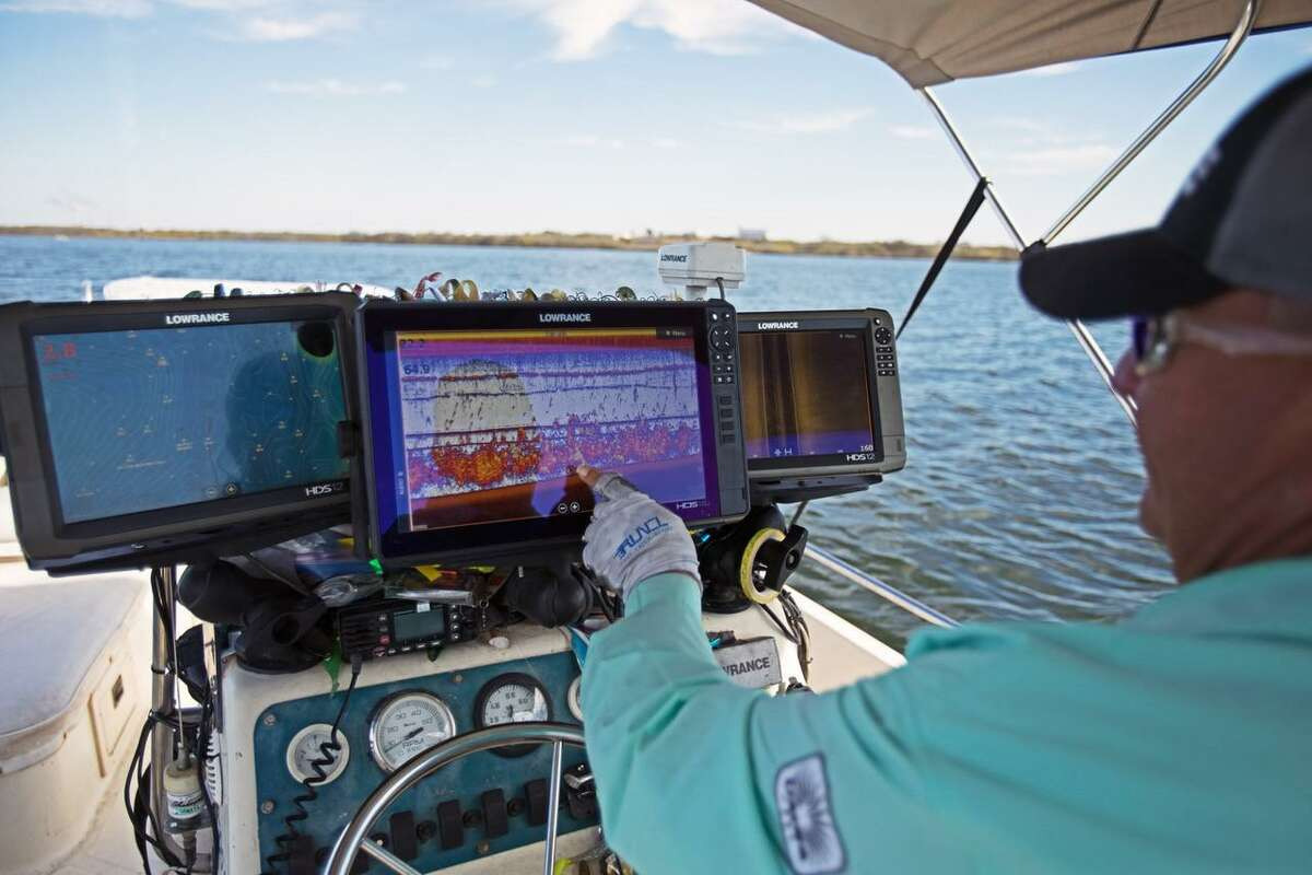 At Braunig Lake, fishing guide Manny Martinez points to a continuous line of baitfish and red drum that stretch across his fish finder almost everywhere he goes, something he has not seen since 1996.