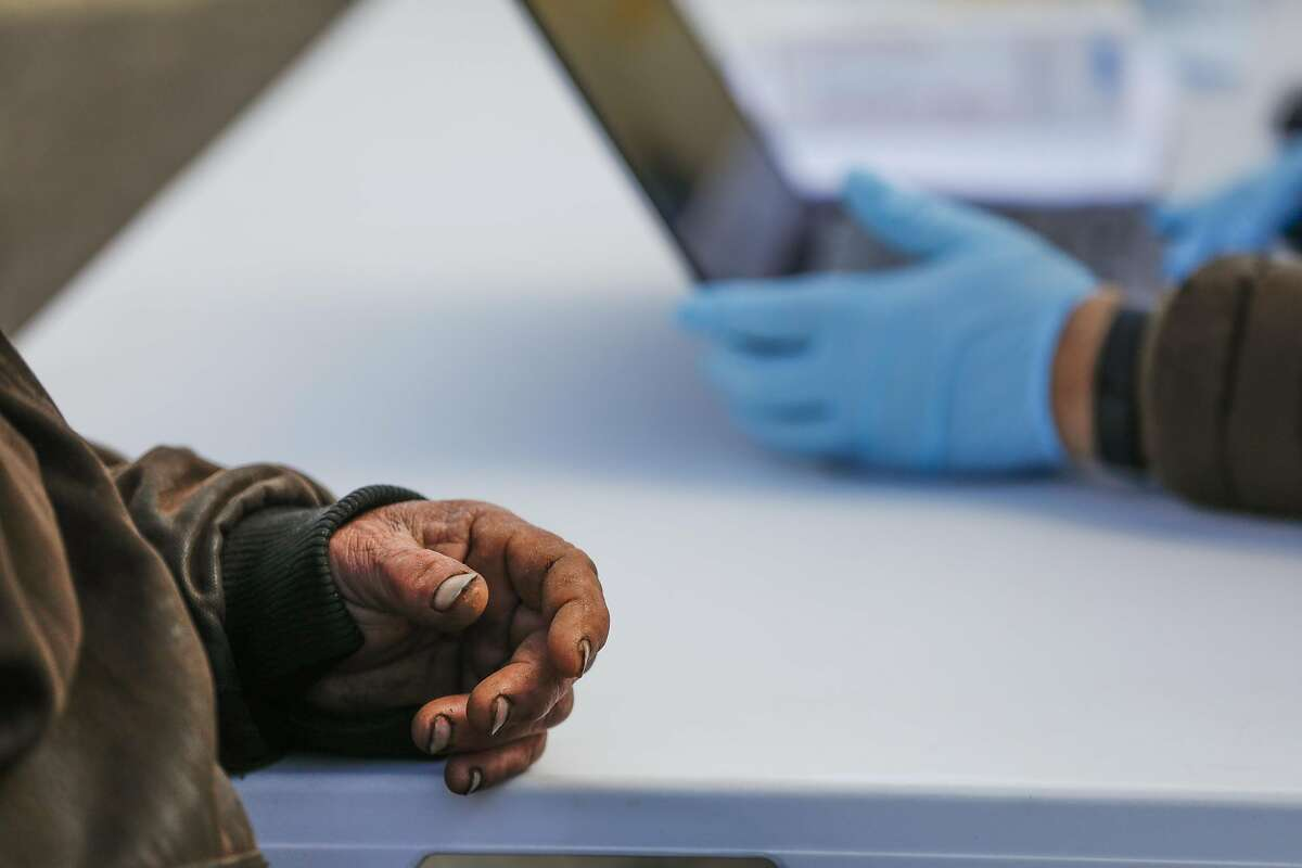 Homeless man Robert Clayton Kerfoot ,57 (left) speaks with Christina Ramirez (right) as he prepares to receive his COVID-19 vaccine from a mobile clinic on Monday, March 15, 2021 in Martinez, California.