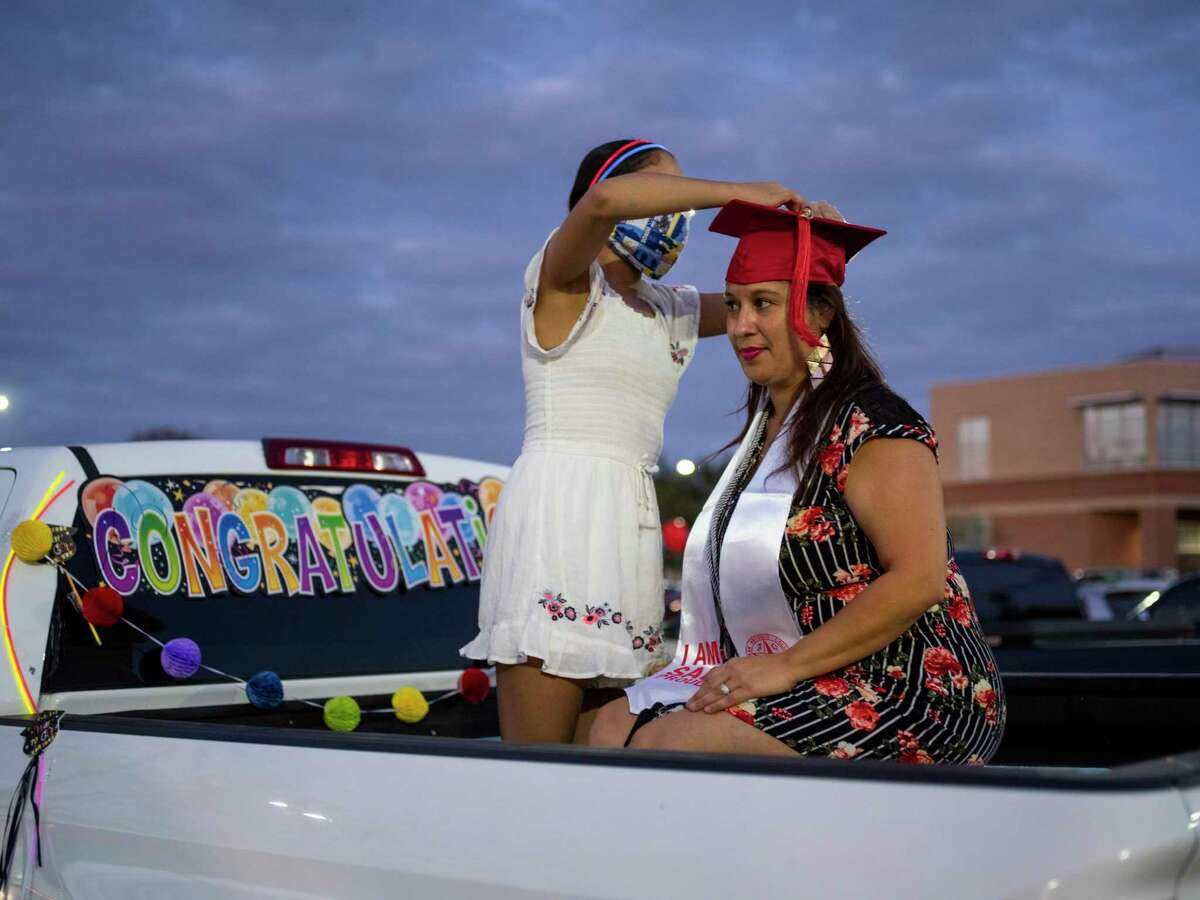 Caprice Diaz, 46, has her graduation tassel fixed to her hat by her daughter, Jessica Diaz, 12, as she celebrates her graduation from San Antonio College last November.