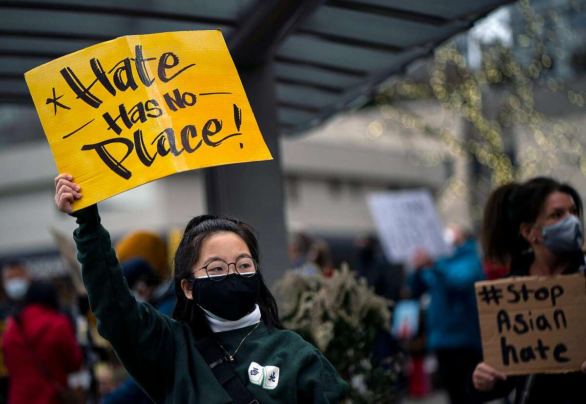 In Bellevue, Wash., a demonstrator holds a sign to resist the rise in violence against Asian Americans.
