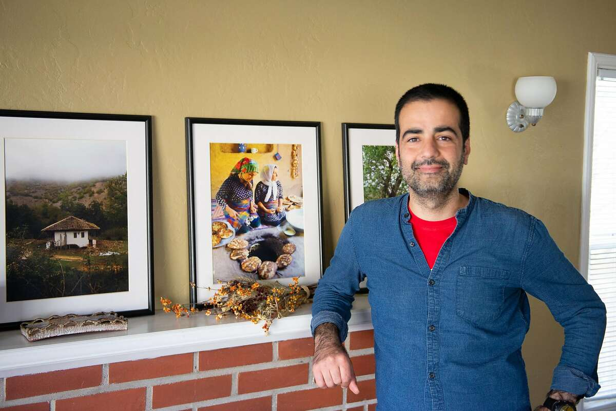 Hanif Sadr, chef and founder of the Northern Iranian pop-up Komaaj, in his living room with photos of women cooking in a village in Gilan Province, Iran on February 7, 2020 in El Cerrito, California.