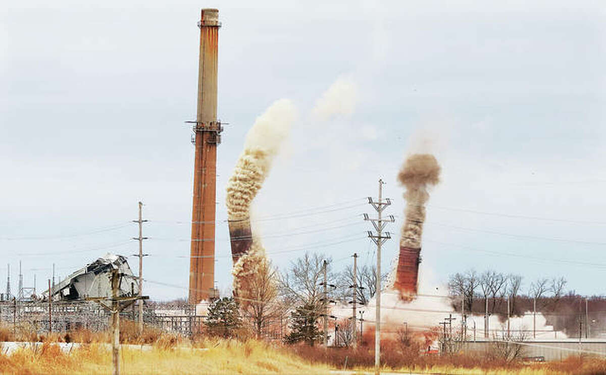 The smokestacks of the former Dynegy Wood River Power Station in East Alton belched out their last puffs early Sunday morning as they headed for the ground during a series of controlled explosions dropping them onto the property.