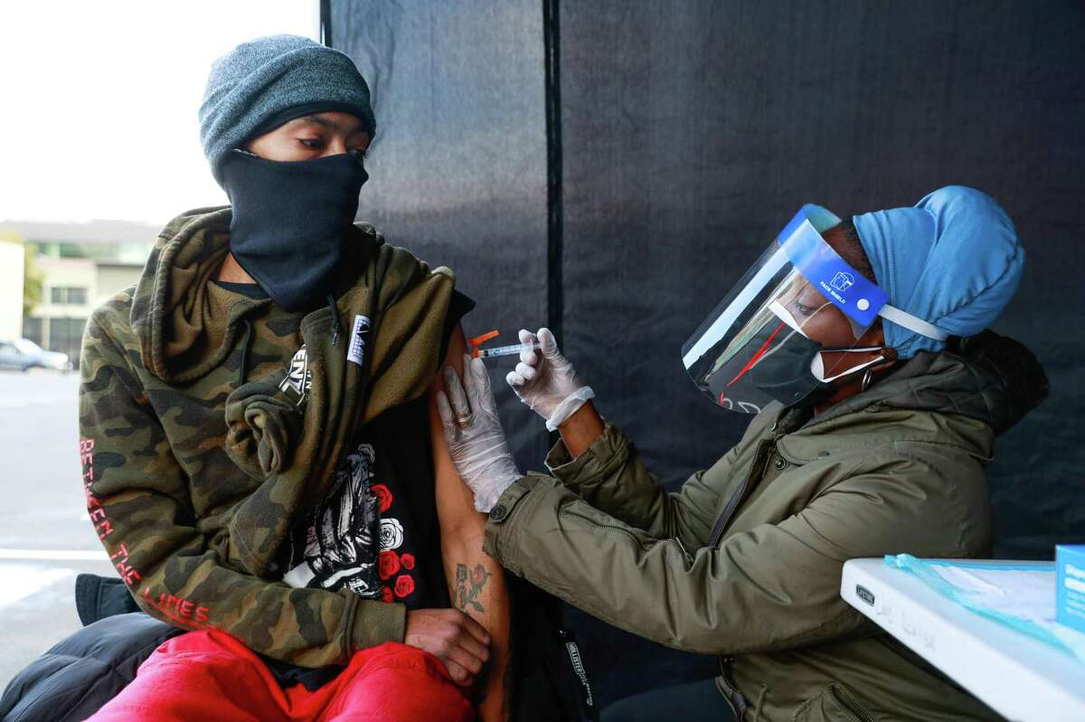 Nurse Sonni Belcher- Collins (right) administers a dose of the Johnson & Johnson COVID-19 vaccine to Vincent Burton (left) on Thursday, March 11, 2021 in Oakland, California. The Trust Clinic hosted a mass vaccination day for people who are unhoused, housing insecure or staff members of the clinic.
