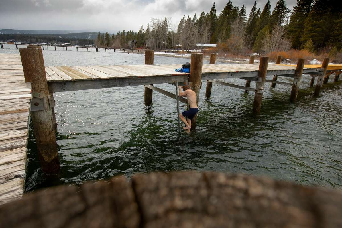 Mitchell climbs down a ladder to get into Lake Tahoe. He never jumps into the lake. He always walks in gradually to ease into the freezing cold water.