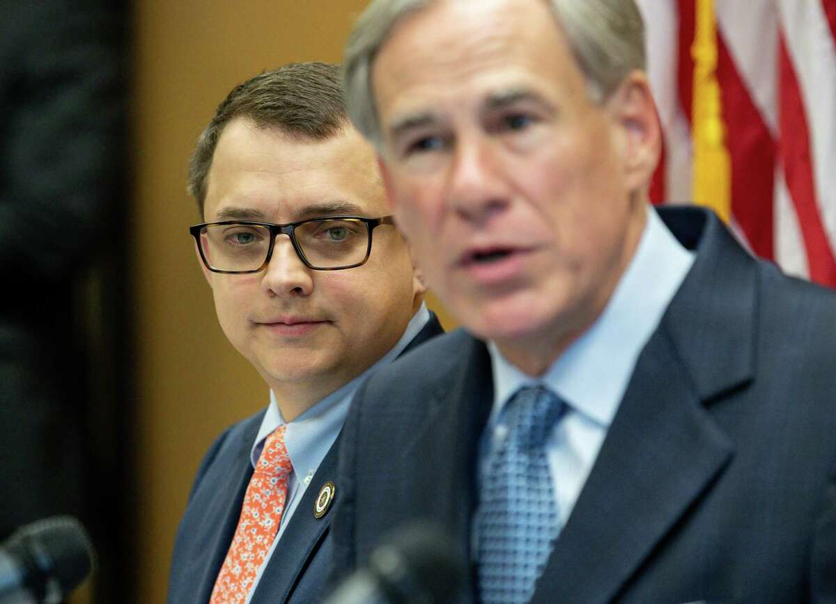 Representative Briscoe Cain, left, listens as Gov. Greg Abbott talks during a press conference last week about a package of election reforms.