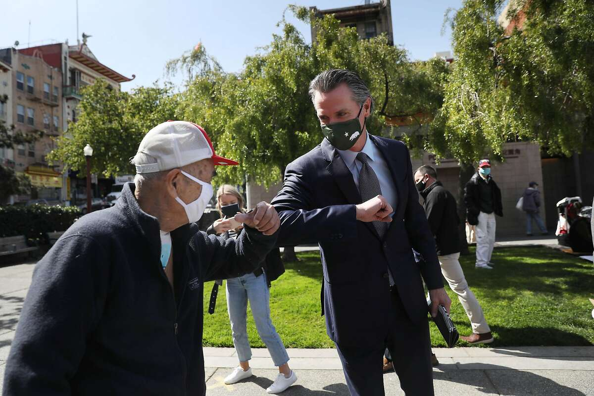 Governor Gavin Newsom elbow bumps a gentlemen as Governor Newsom walks through Portsmouth Square after meeting with Bay Area Asian American and Pacific Islander (AAPI) community leaders at the Chinese Culture Center of San Francisco and speaking to the media amid the rise in racist attacks across the country on Friday, March 19, 2021 in San Francisco, Calif.