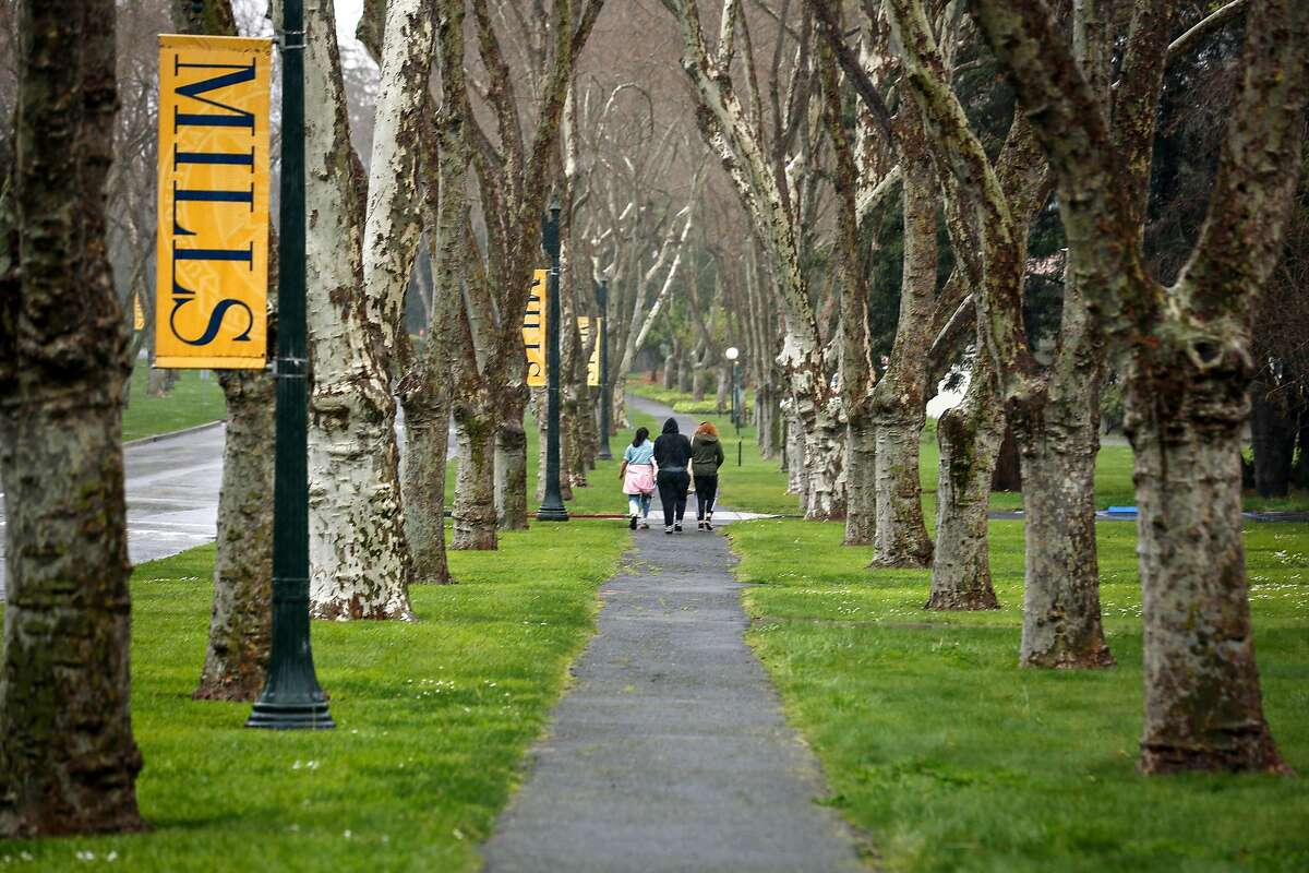 A group of woman walk through the iconic row of trees on Mills College campus on Thursday, March 18, 2021 in Oakland, Calif. One of the oldest and last women's colleges in the country, Oakland's Mills College, is winding down, and is no longer enrolling first-year students.