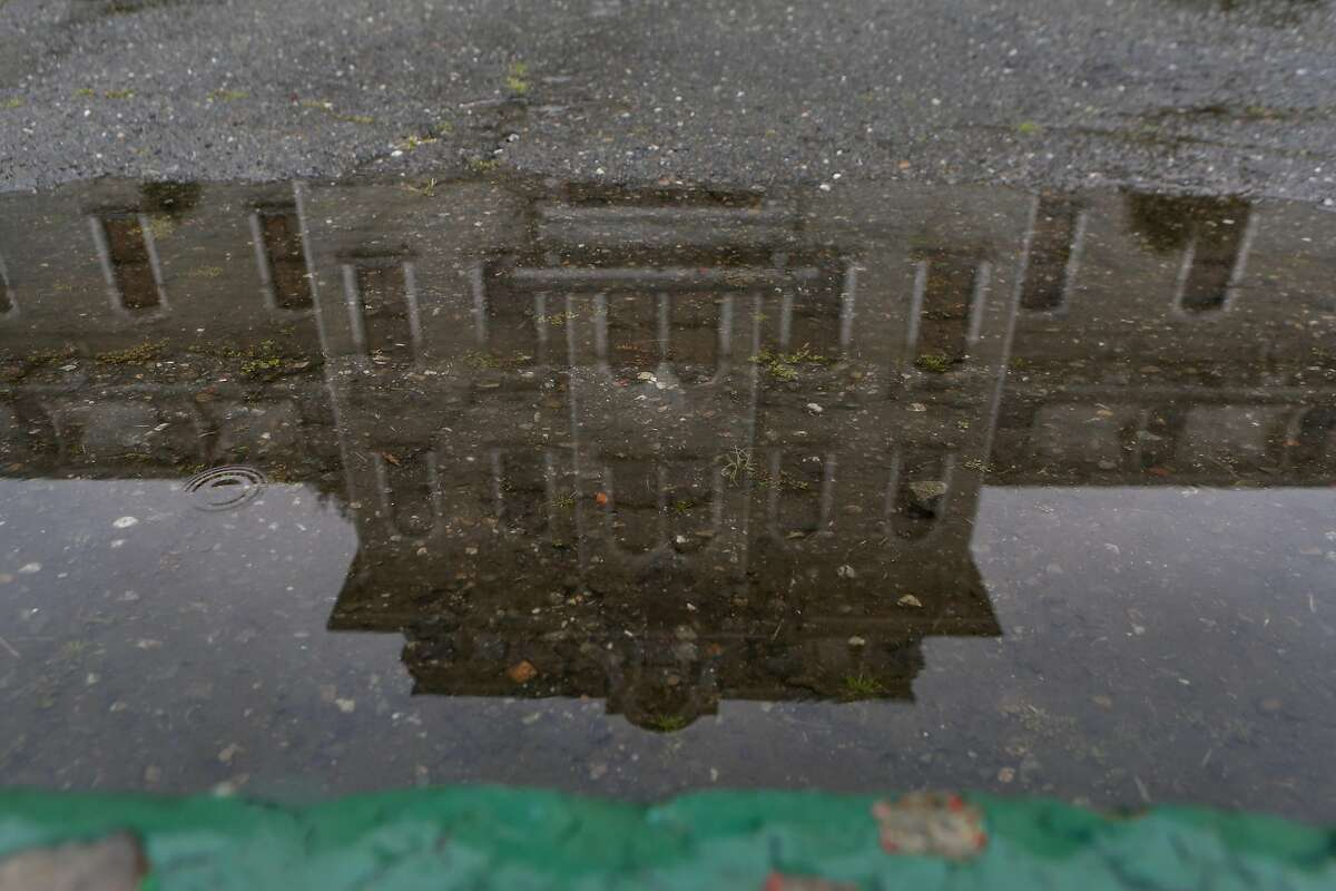 Mill Hall is seen reflected in a puddle at Mills College in Oakland. One of the oldest and last women's colleges in the country, Mills College is winding down and will no longer enroll first-year students.