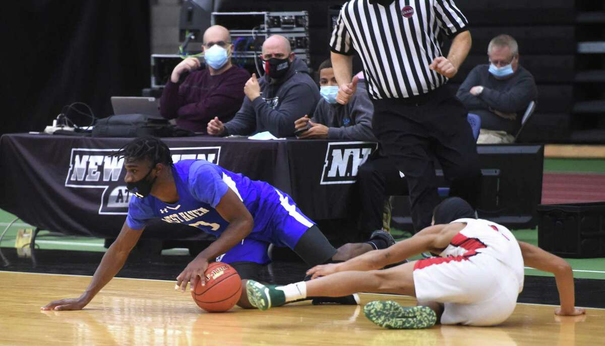 West Haven's Malcolm Duncanson, left, and Wilbur Cross' Dereyk Grant fight for a loose ball.