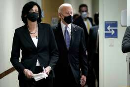 Dr. Rochelle Walensky, director of the Centers for Disease Control and Prevention, leads President Joe Biden into the room for a COVID-19 briefing at the headquarters for the CDC, Friday, March 19, 2021, in Atlanta.