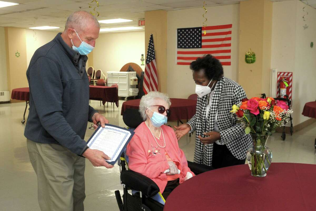 Mayor Mark Lauretti hands a proclamation to Sophie Pollock during a birthday party at Hewitt Health and Rehabilitation Center, in Shelton, Conn. March 19, 2021. Pollock turned 102 this week. Lauretti and Pollock are seen here with Hewitt recreation director Zaida Stewart.