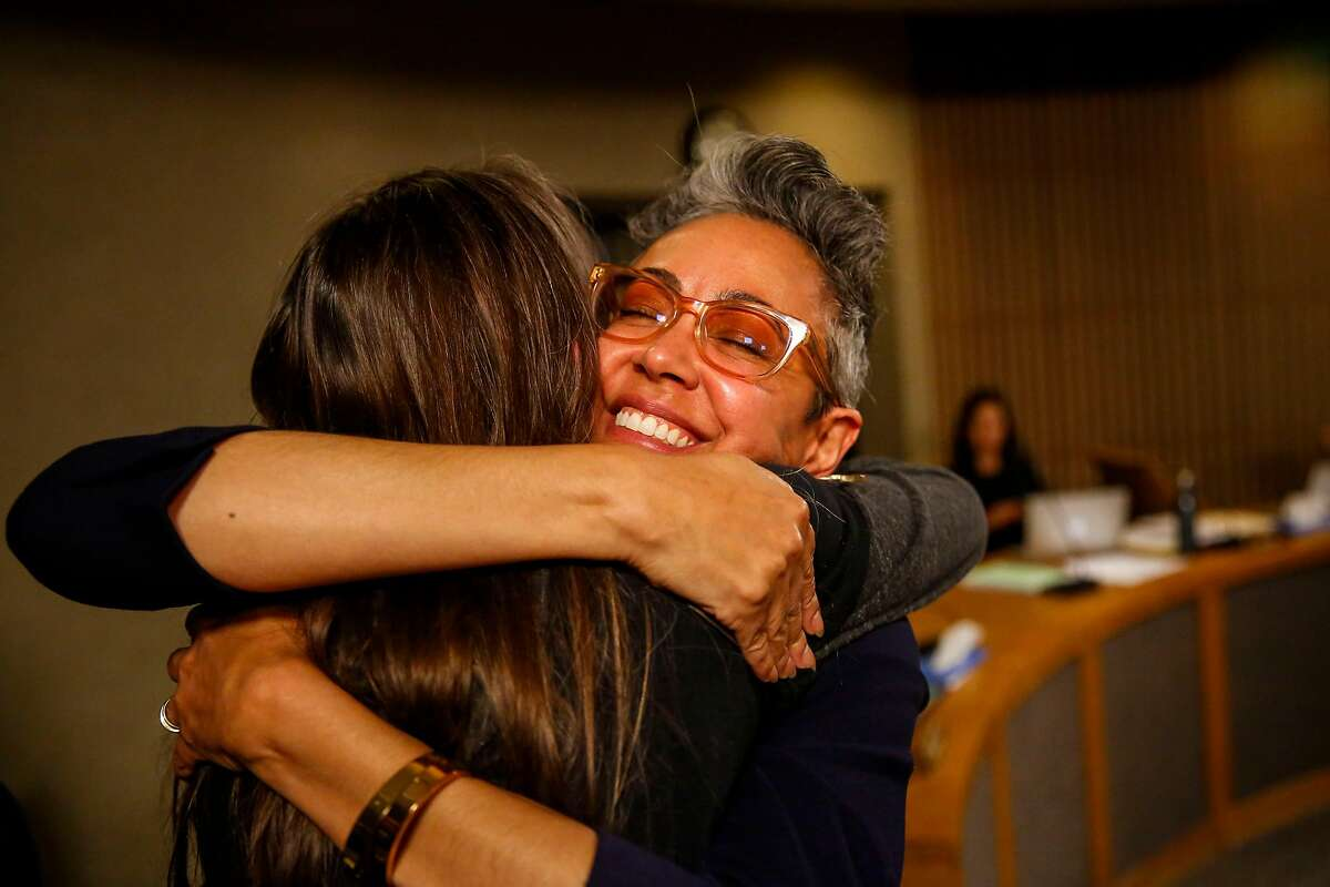School board member Alison Collins hugs organizer Amy Anderson during the San Francisco Unified School District school board meeting where the board voted to remove or cover a controversial mural at George Washington High School in June 2019.