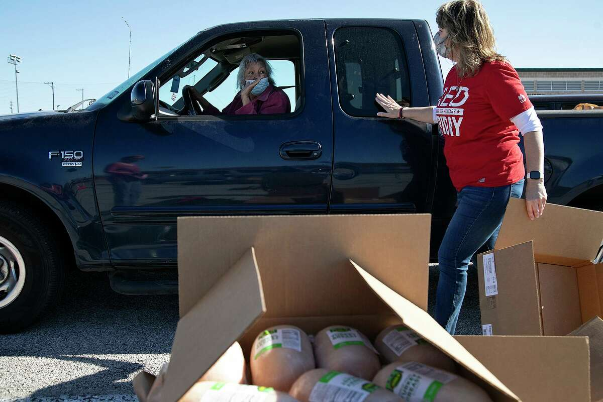 Ernestina Hernandez, in the truck, picks up food with the help of volunteer Linda Eaton during the San Antonio Food Bank's mega food distribution at Gustafson Stadium in San Antonio on March 19, 2021. Hernandez picked up extra bread to make sandwiches for homeless people in her community.