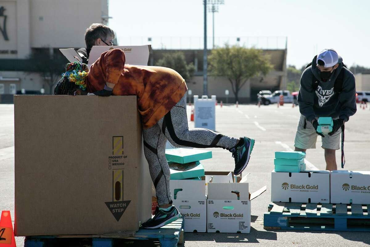 Volunteer Alysa McLaurin reaches to the bottom of a box for the few remaining baked goods to give out during the San Antonio Food Bank's mega food distribution at Gustafson Stadium in San Antonio on March 19, 2021.