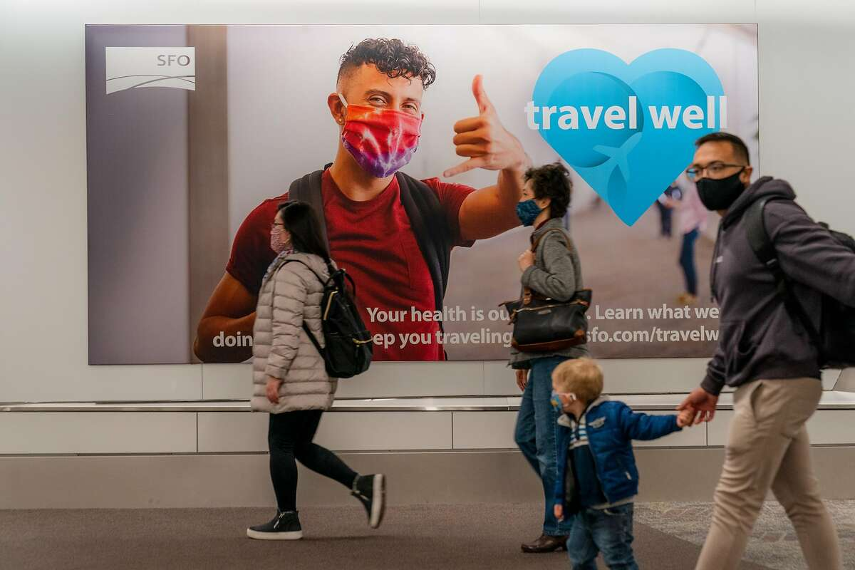 A family walks past a sign urging safe travel during the pandemic at San Francisco International Airport on Friday, December 18, 2020. A young boy traveling in Hawaii with his family died after contracting COVID-19 - making the case the state's first pediatric fatality from the coronavirus.