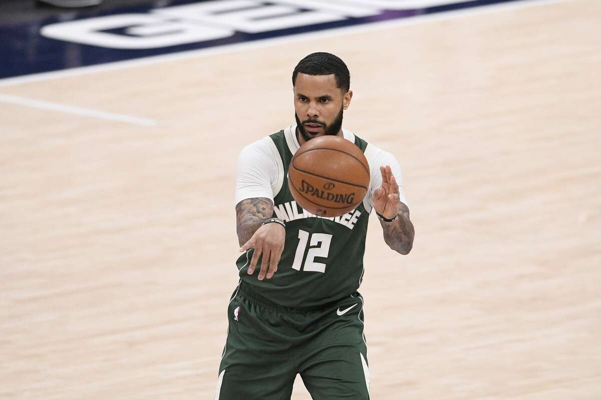 Milwaukee Bucks guard D.J. Augustin (12) passes during the first half of an NBA basketball game against the Washington Wizards, Monday, March 15, 2021, in Washington. (AP Photo/Nick Wass)