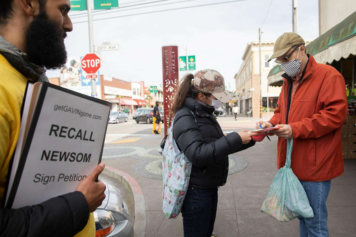Carlo Mastrogiacomo of San Francisco signs a petition to recall Gavin Newsom outside the 22nd & Irving Market in San Francisco on March 2, 2021.