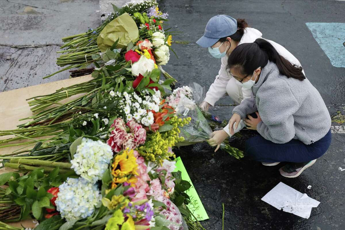 Jenny Choi, left, and Kristi You place flowers at the entrance of Gold Spa, one of three Atlanta-area locations where deadly shootings happened this week. Six of the eight people killed were Asian women.