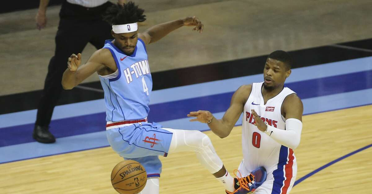 The ball slips out of Houston Rockets forward Danuel House Jr.'s (4) hand while Detroit Pistons guard Dennis Smith Jr. (0) is defensing during the second quarter of the NBA game Friday, March 19, 2021, at Toyota Center in Houston.