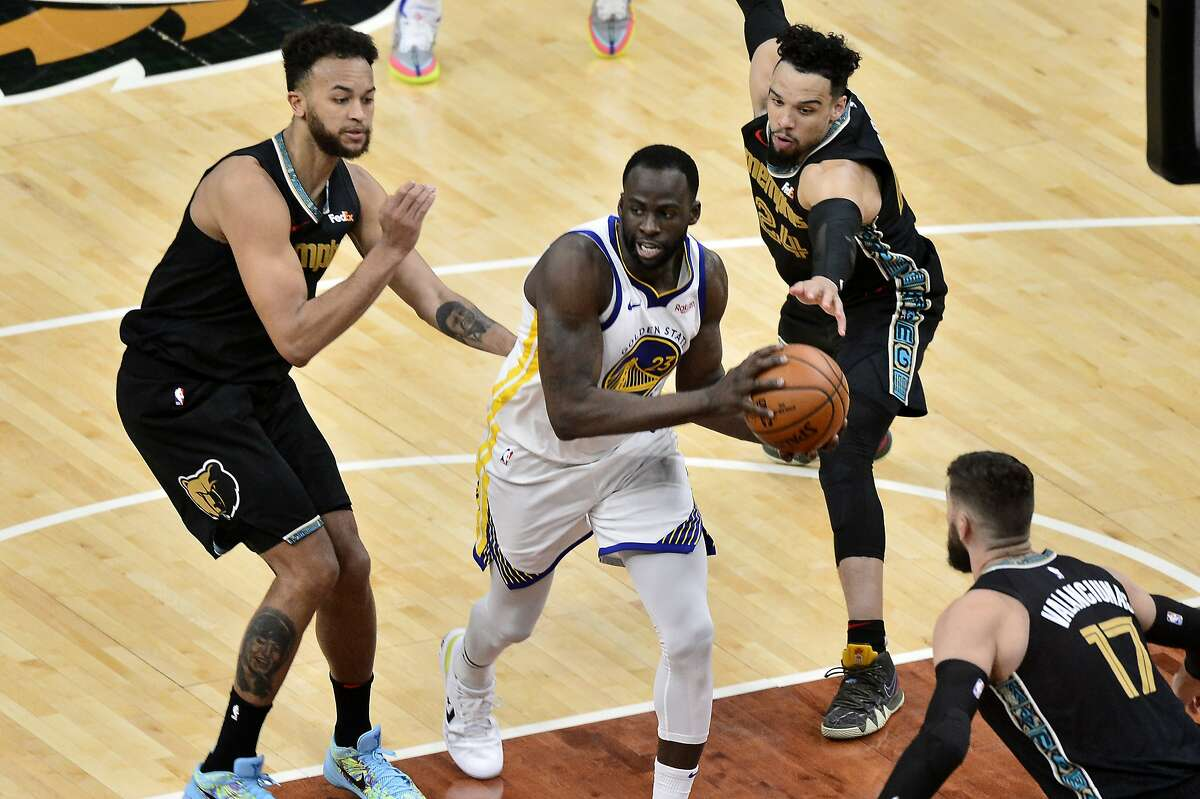 Golden State Warriors forward Draymond Green (23) handles the ball between Memphis Grizzlies forwards Dillon Brooks (24) and Kyle Anderson (1) in the second half of an NBA basketball game Friday, March 19, 2021, in Memphis, Tenn. (AP Photo/Brandon Dill)