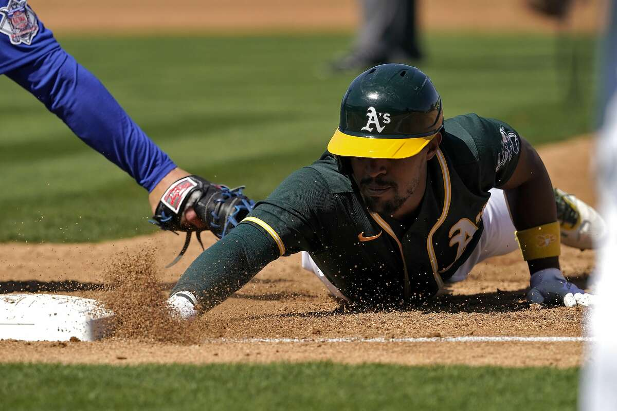 A's left fielder Tony Kemp, who had been hit by a pitch, dives back safely into first base on a second-inning pick-off attempt by Cubs starter Kyle Davies. Kemp was 0-2 in the game.