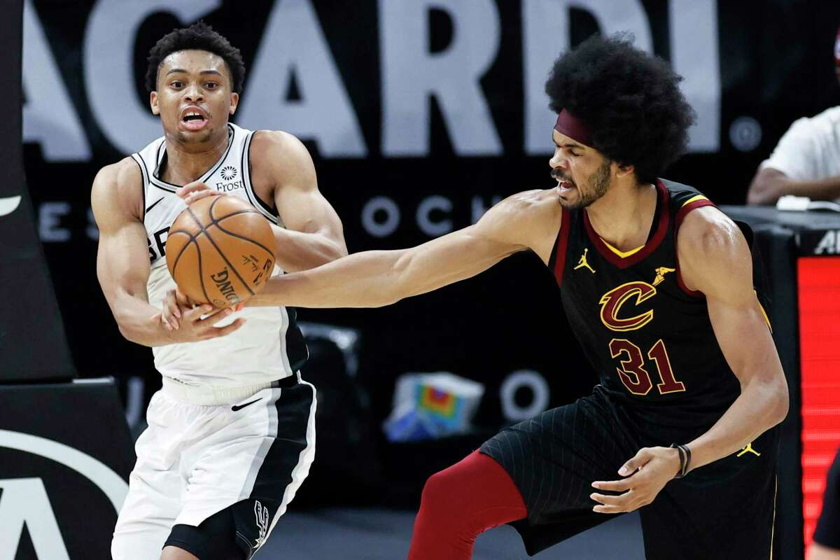 San Antonio Spurs' Keldon Johnson (3) grabs a rebound against Cleveland Cavaliers' Jarrett Allen (31) in the second half of an NBA basketball game, Friday, March 19, 2021, in Cleveland. (AP Photo/Ron Schwane)