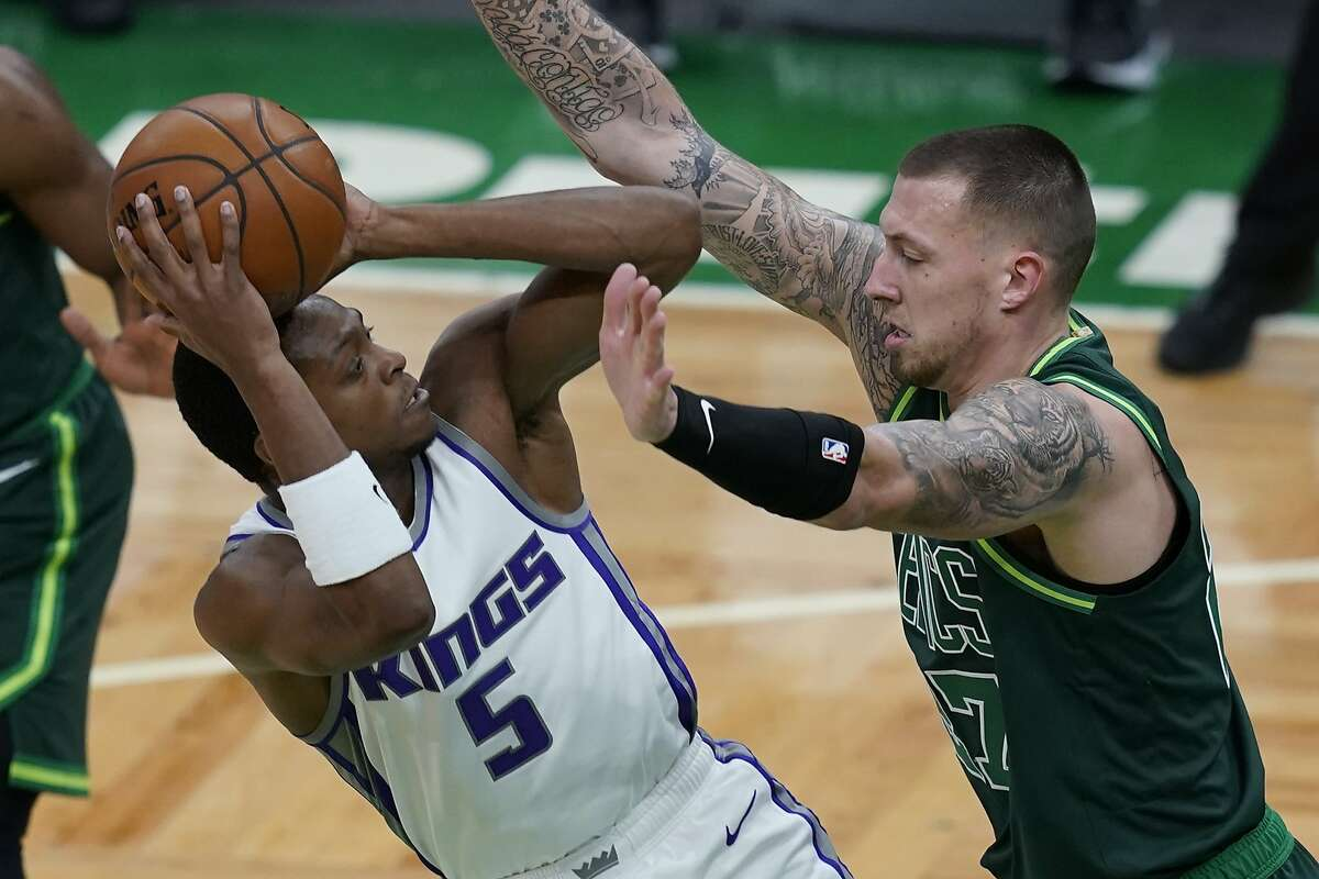Sacramento Kings guard De'Aaron Fox (5) shoots against Boston Celtics center Daniel Theis, right, in the first quarter of an NBA basketball game, Friday, March 19, 2021, in Boston. (AP Photo/Elise Amendola)