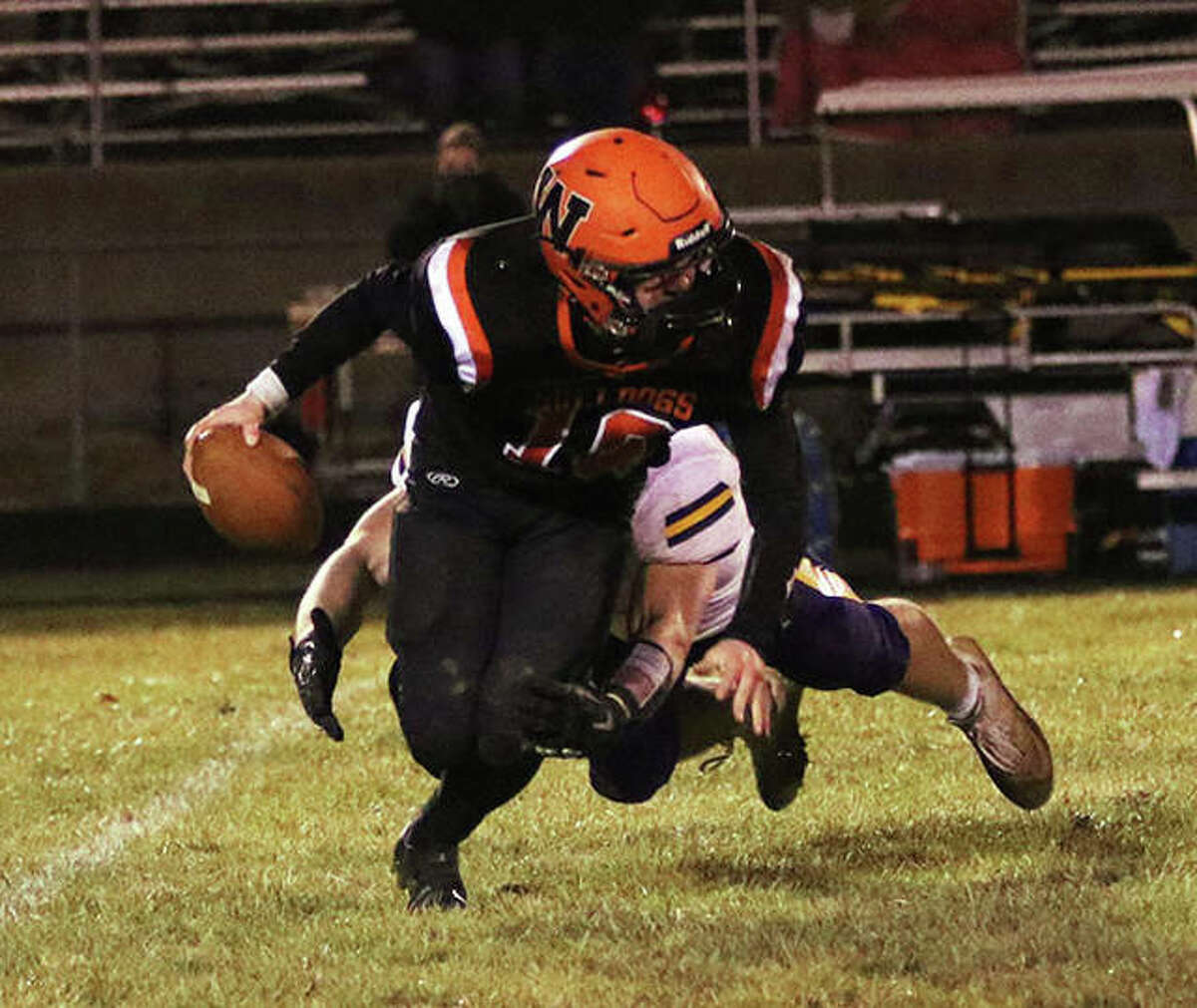 Waterloo QB Eric Brown (front) cannot escape the rush from CM defensive lineman Cole Stimac, who takes Brown down for a sack on third down to force Bulldogs punt in the third quarter Friday night in Waterloo.