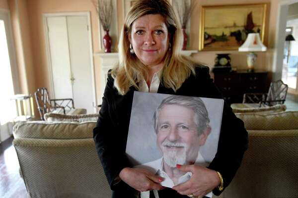 Kathy Thomas holds a photo of her husband, Dr. George Thomas, who died Dec.12 from COVID-19. Dr. Thomas treated coronavirus patients from the onset of the pandemic in the area, believing it was a time when his skills were needed more than ever before. The family plans a memorial service later in the spring. Photo made Saturday, March 20, 2021 Kim Brent/The Enterprise