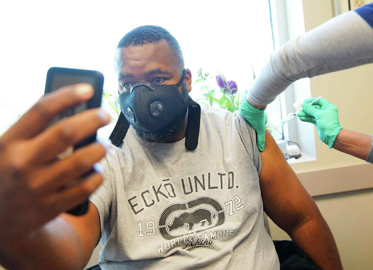 Army Veteran Samuel Dominique, 42, of Conroe, Texas takes a selfie as he gets his first COVID-19 at the Conroe VA Clinic on Saturday, March 20, 2021. The walk-in vaccine clinic was open to veterans of all ages.