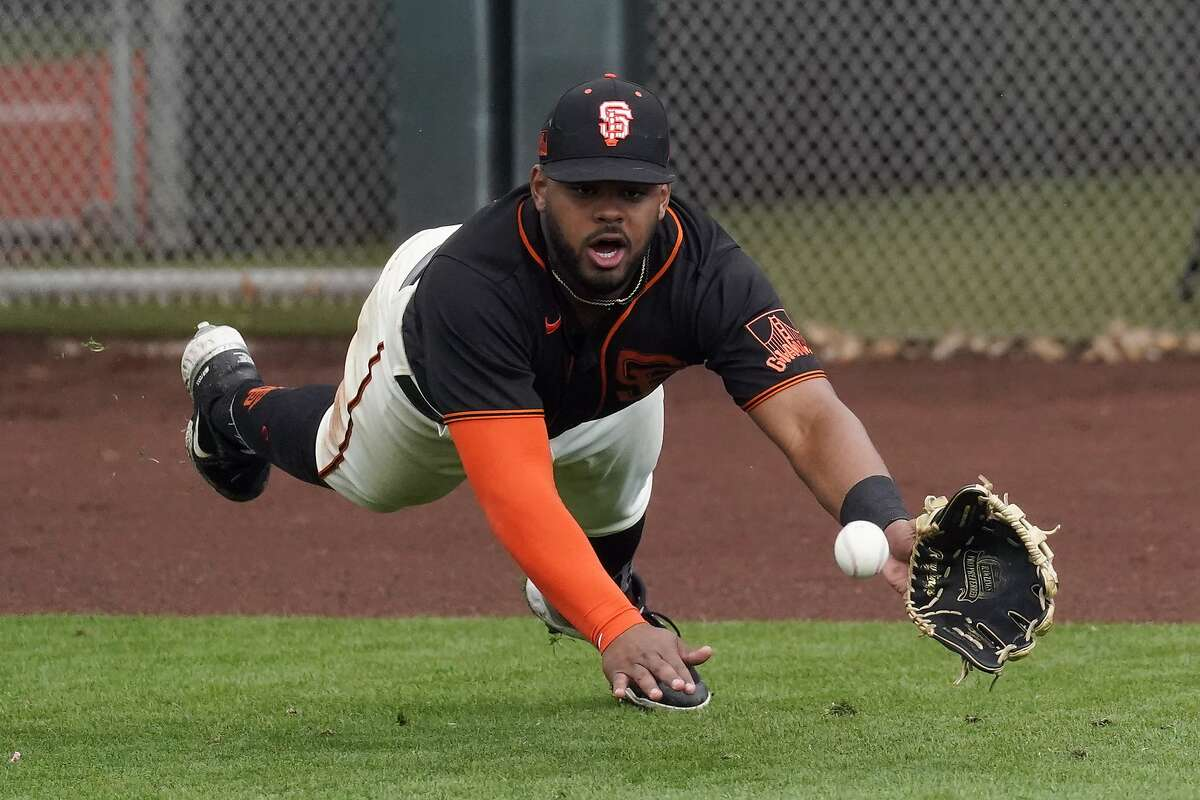 San Francisco Giants right fielder Heliot Ramos dives to try to catch a fly ball hit by Colorado Rockies' Alan Trejo during the eighth inning of a spring training baseball game Friday, March 12, 2021, in Scottsdale, Ariz. Ramos did not catch the ball and Trejo doubled. (AP Photo/Ashley Landis)