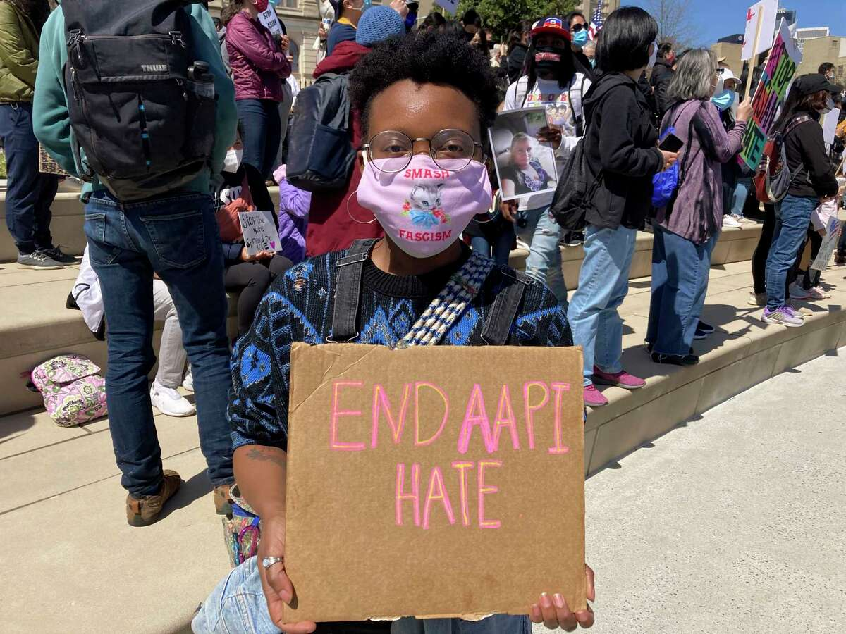 """Camden Hunt poses for a picture at a rally on Saturday, March 20, 2021, across from the Georgia state Capitol in Atlanta to demand justice for the victims of shootings at massage businesses days earlier. A 21-year-old white man is accused of killing eight people, six of them women of Asian descent, at three Atlanta-area massage businesses Tuesday. Hunt said she came out to the rally Saturday to """"show Black and Asian solidarity."""""""