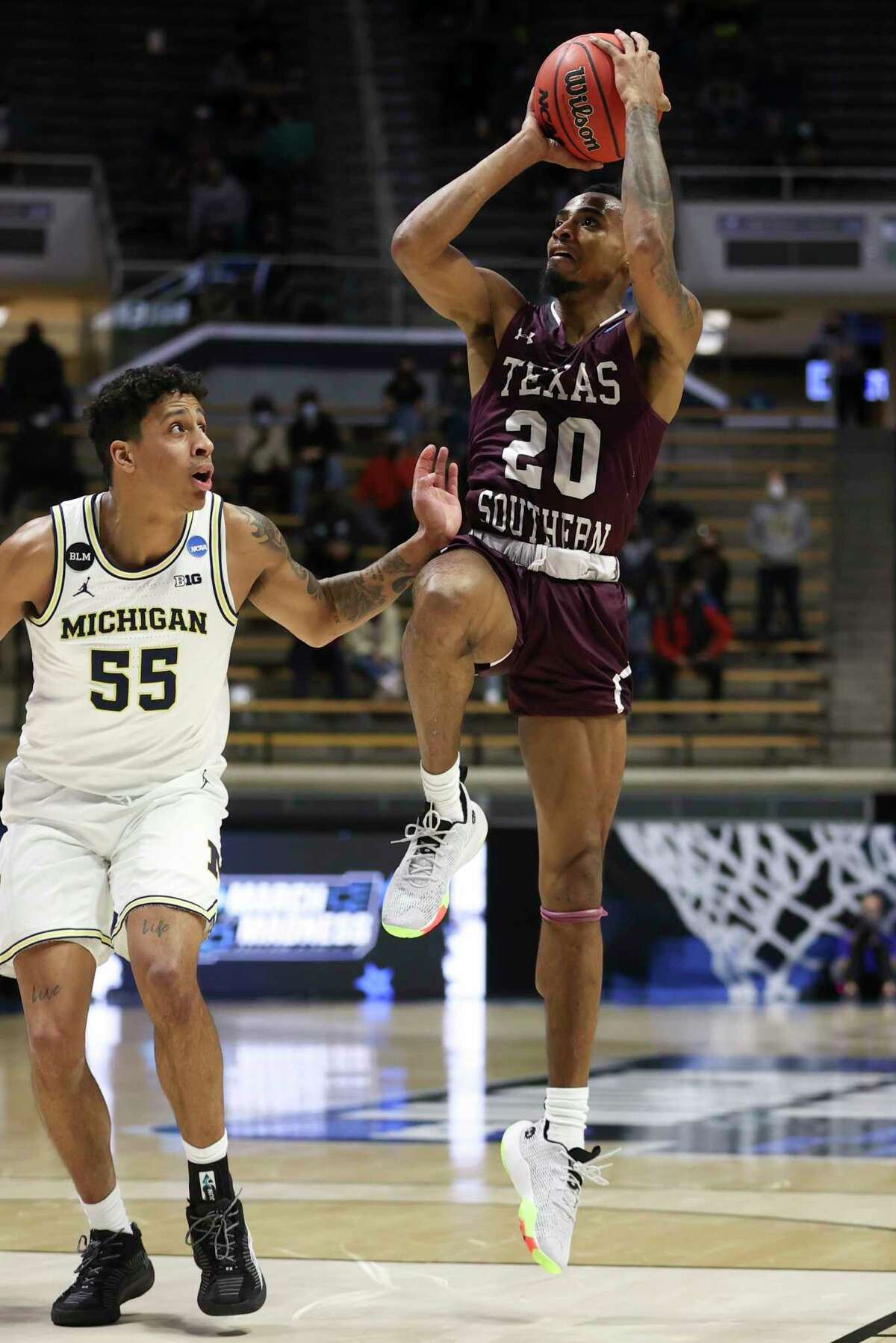 WEST LAFAYETTE, INDIANA - MARCH 20: Michael Weathers #20 of the Texas Southern Tigers shoots against Eli Brooks #55 of the Michigan Wolverines during the first half in the first round game of the 2021 NCAA Men's Basketball Tournament at Mackey Arena on March 20, 2021 in West Lafayette, Indiana.