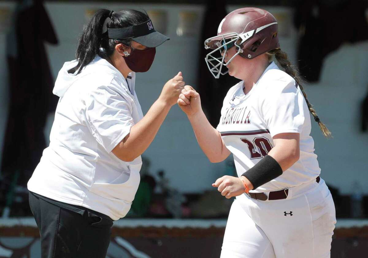 FILE - Magnolia's Jamie Holder gets a fist-bump from head coach Angela Cooper after her two-run home run in the first inning of a District 19-5A high school softball game at Magnolia High School, Saturday, March 20, 2021, in Magnolia.