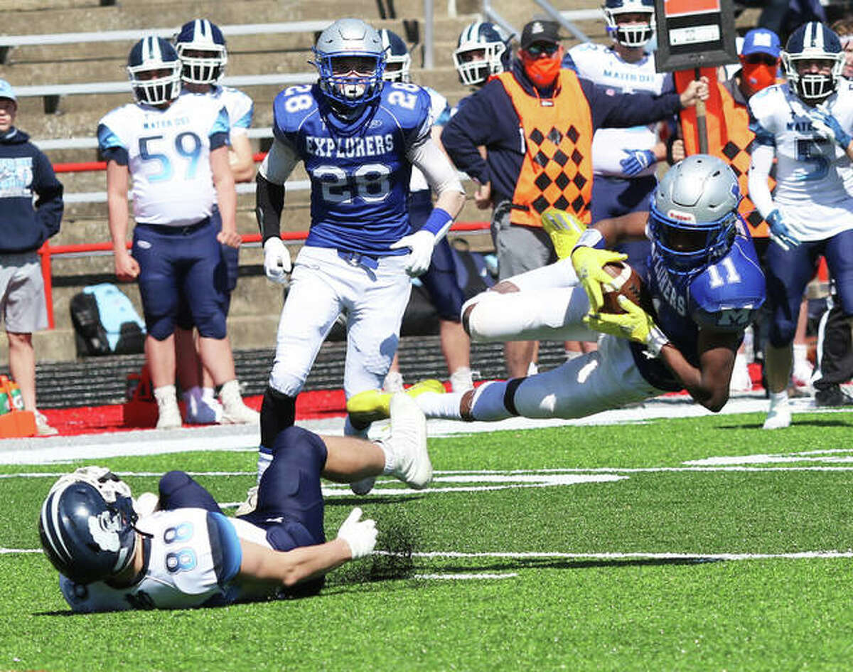 Marquette Catholic's Devon Fields (11) makes a diving attempt at a catch after beating Breese Mater Dei's Mitchell Haake (88) to the football as the Explorers' Alex Barnhart (28) watches the play on Saturday afternoon at Public School Stadium in Alton.