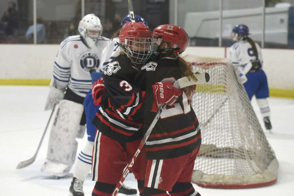 New Canaan's Grace Crowell (22) and Courtney O'Connell (3) celebrate after Crowell's second-period goal tied Darien at 1-1 during the FCIAC girls ice hockey championship game at the Darien Ice House on Saturday, March 20, 2021.