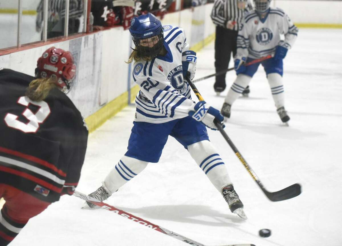 Darien's Nelle Kniffin (20) takes a shot while New Canaan's Courtney O'Connell (3) defends during the FCIAC girls ice hockey championship game at the Darien Ice House on Saturday, March 20, 2021.