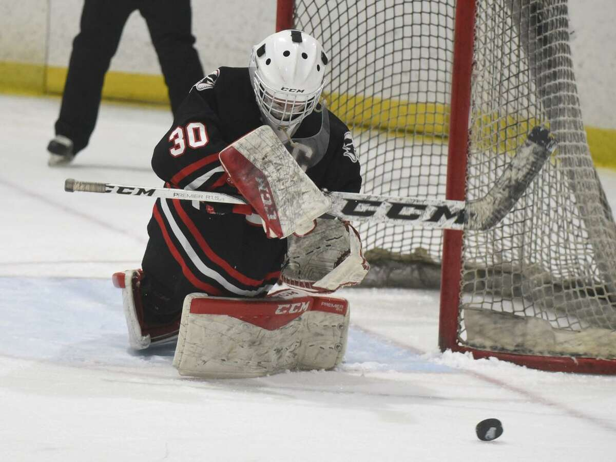 New Canaan's goalie Blythe Novick (30) knocks the puck away against Darien during the FCIAC girls ice hockey championship game at the Darien Ice House on Saturday, March 20, 2021.