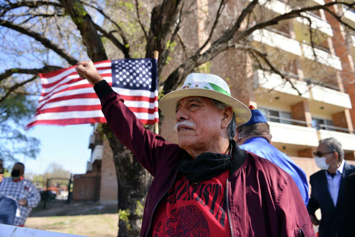 LULAC Executive Director Henry Rodriguez raises his fist as he protests Saturday outside the Fair Avenue Apartments on the Southwest Side, blaming the San Antonio Housing Authority and city for a continuing lack of accountability in the February winter storm and power outages.