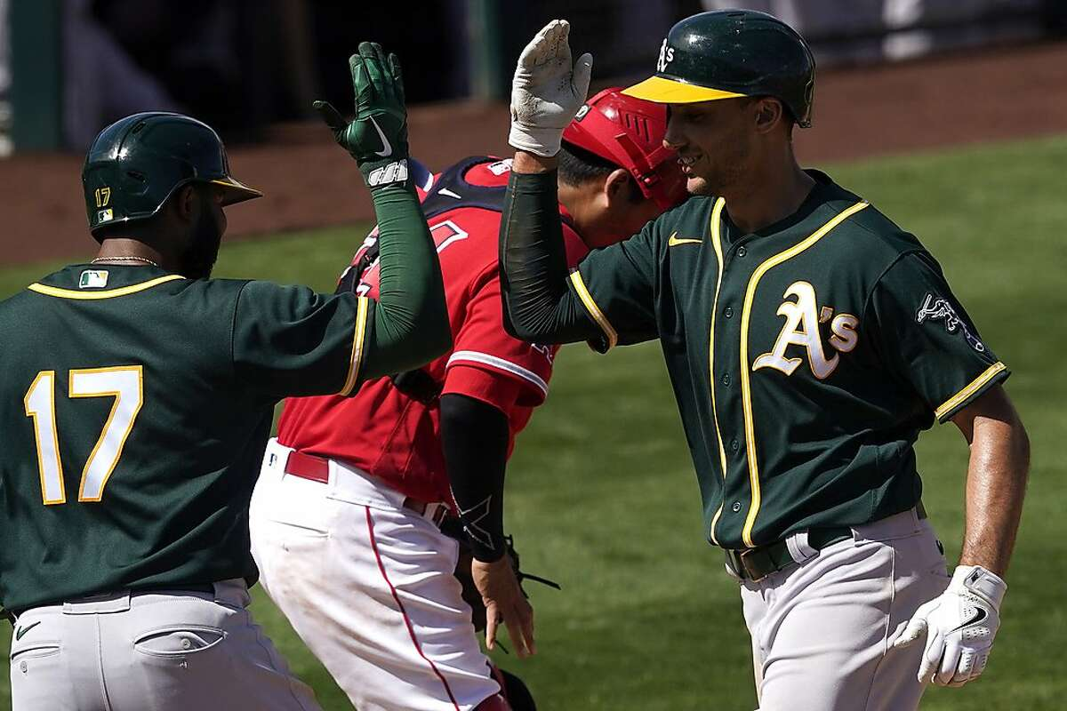 Oakland Athletics' Matt Olson high fives teammate Elvis Andrus (17) after hitting a two run home run against the Los Angeles Angels during the third inning of a spring training baseball game, Saturday, March 20, 2021, in Tempe, Ariz. (AP Photo/Matt York)