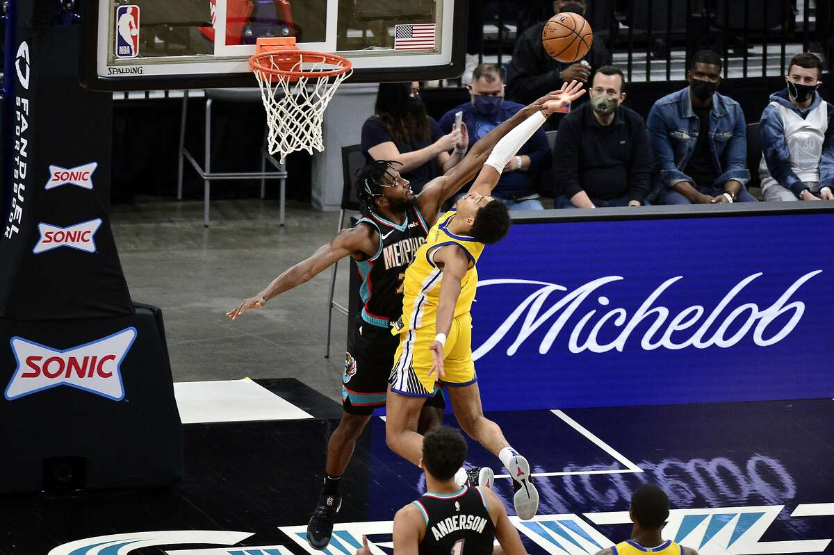 Golden State Warriors guard Jordan Poole, right, shoots against Memphis Grizzlies forward Justise Winslow in the first half of an NBA basketball game Saturday, March 20, 2021, in Memphis, Tenn. (AP Photo/Brandon Dill)