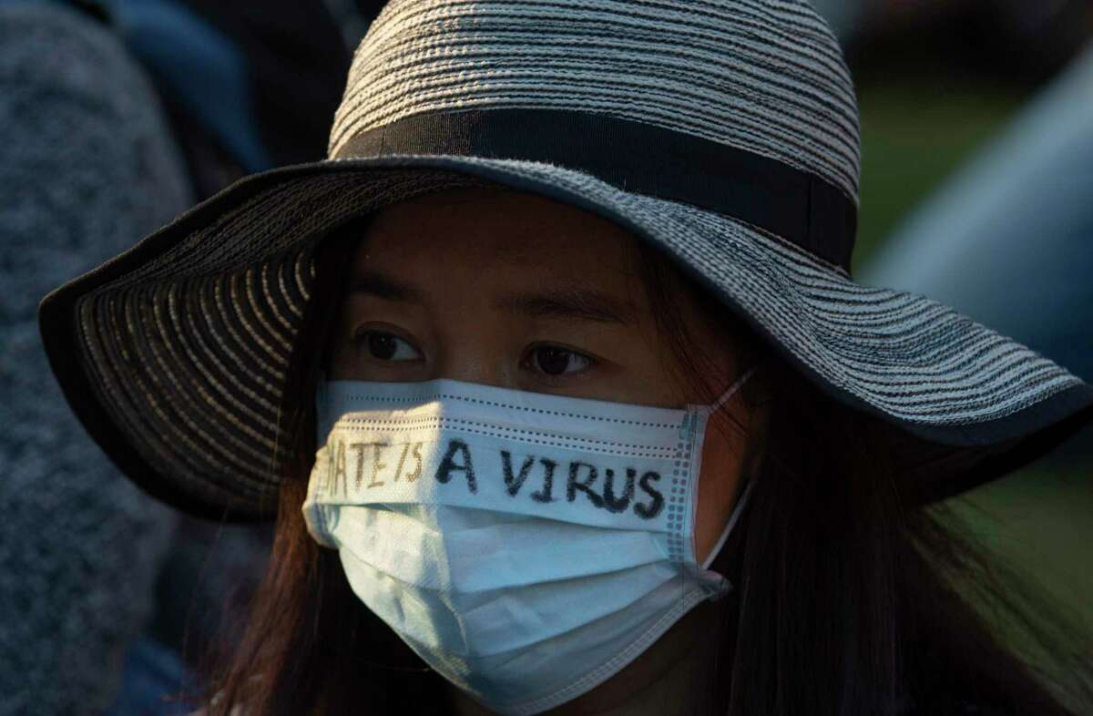 """Bingning Dong, wearing a """"Hate Is A Virus"""" mask, takes a moment of silence while participating a """"Stop Asian Hate Vigil & Rally"""" to mourn the six Asian American victims killed in Atlanta and denounce a rise in hate incidents and violence targeting Asian Americans Saturday, March 20, 2021, at Discovery Green in Houston."""