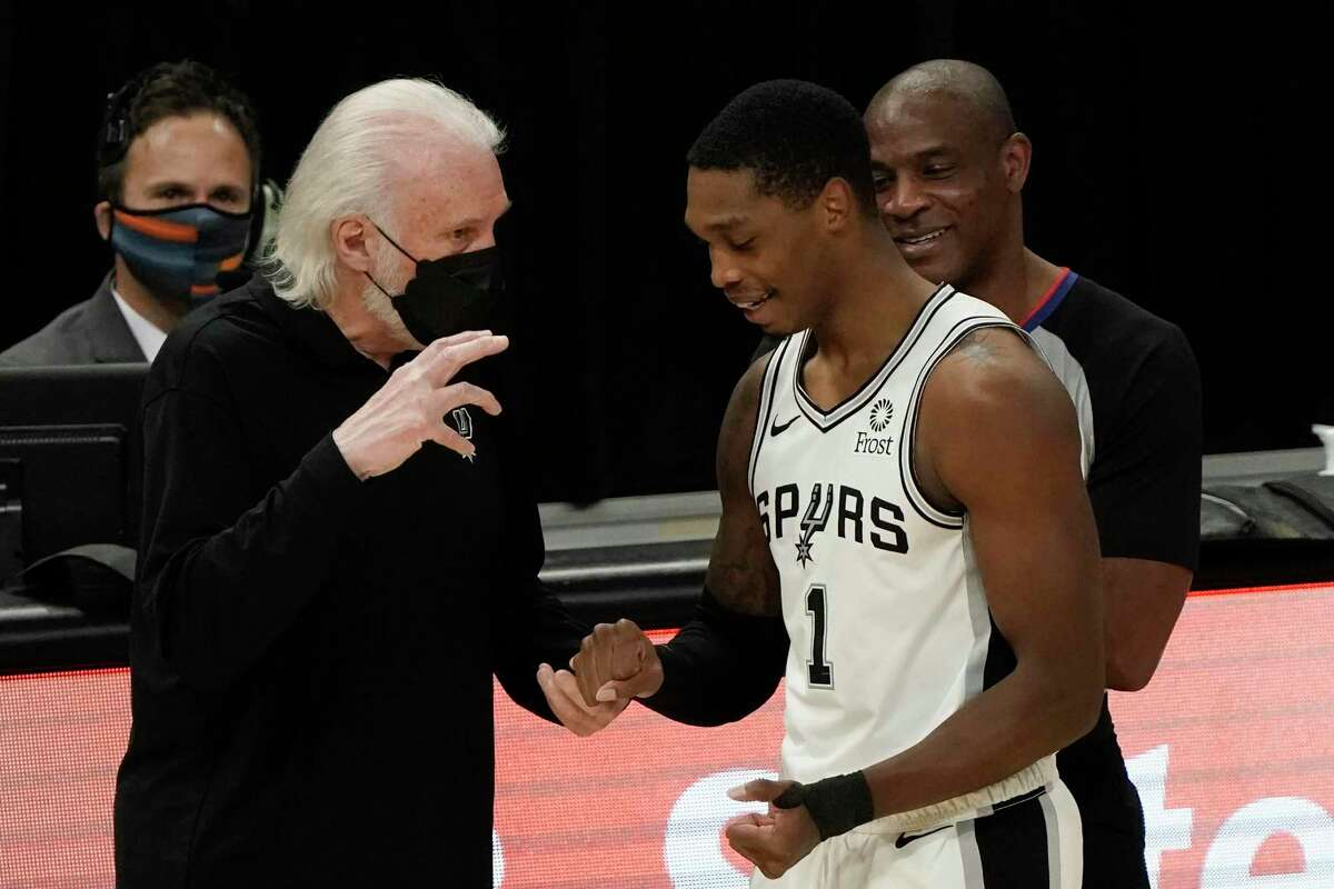 Spurs head coach Gregg Popovich talks tpo Lonnie Walker IV during the first half of an NBA game against the Milwaukee Bucks on Saturday, March 20, 2021, in Milwaukee.