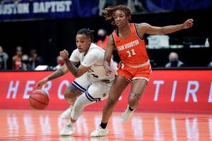Stephen F. Austin guard Zya Nugent (22) drives around Sam Houston State forward Courtney Cleveland (11) during the second half of an NCAA college basketball game for the Southland Conference women's tournament championship Sunday, March 14, 2021, in Katy, Texas.